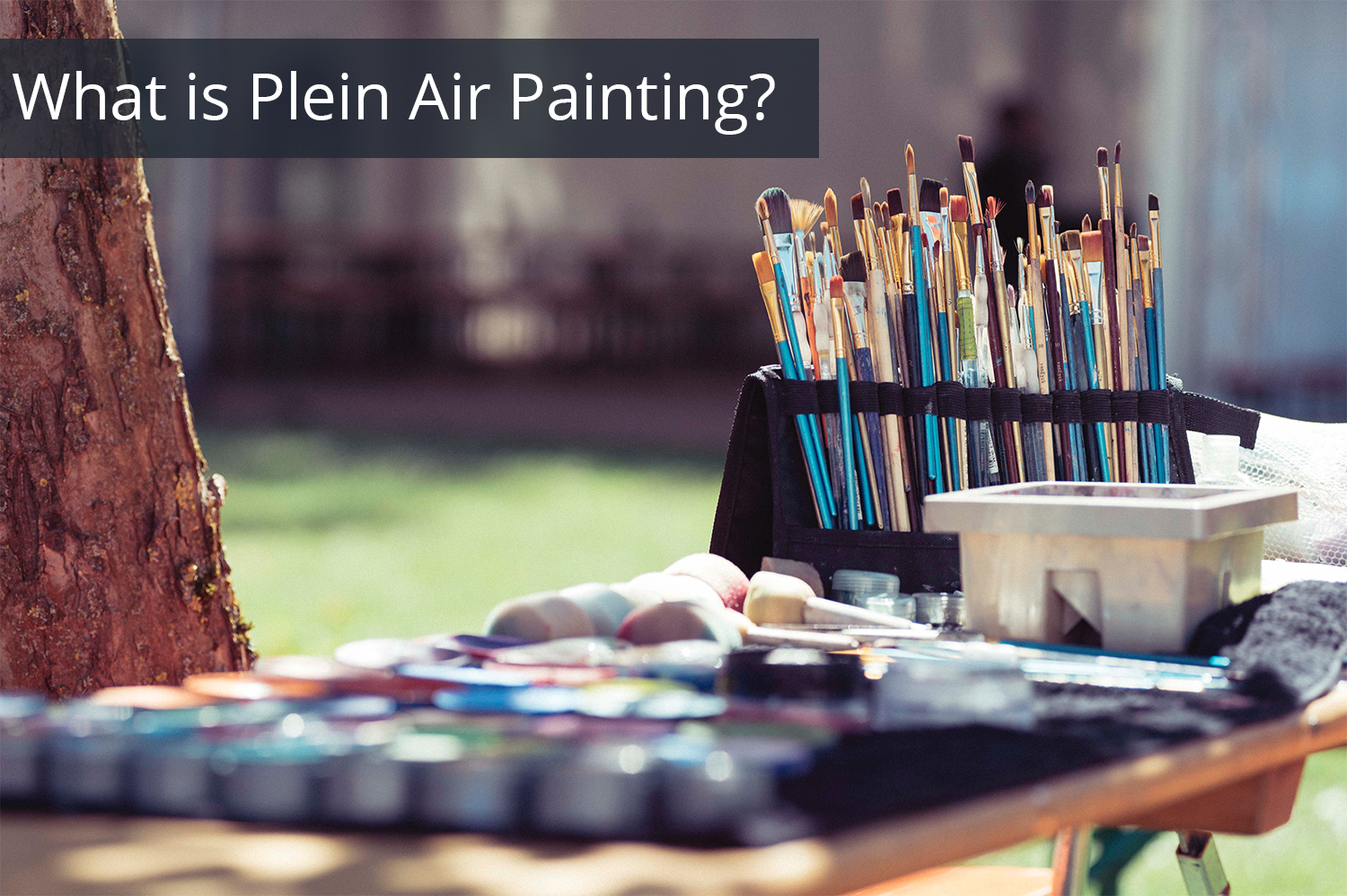 Paint, paint brushes, art supplies and a canvas on an easel set outside.