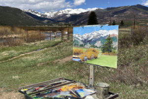 Plein air painting set up on easel outside in front of mountains with paints and brushes in front of it.