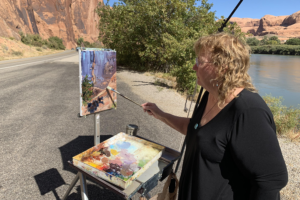 Sharon Marquez painting en plein air on the side of a rode.