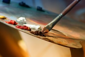 A painter's palette with a brush dipping into oil paint, ready to start an alla prima painting.