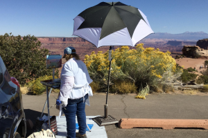 Sharon painting an oil painting alla prima outside with a shade umbrella to her right.